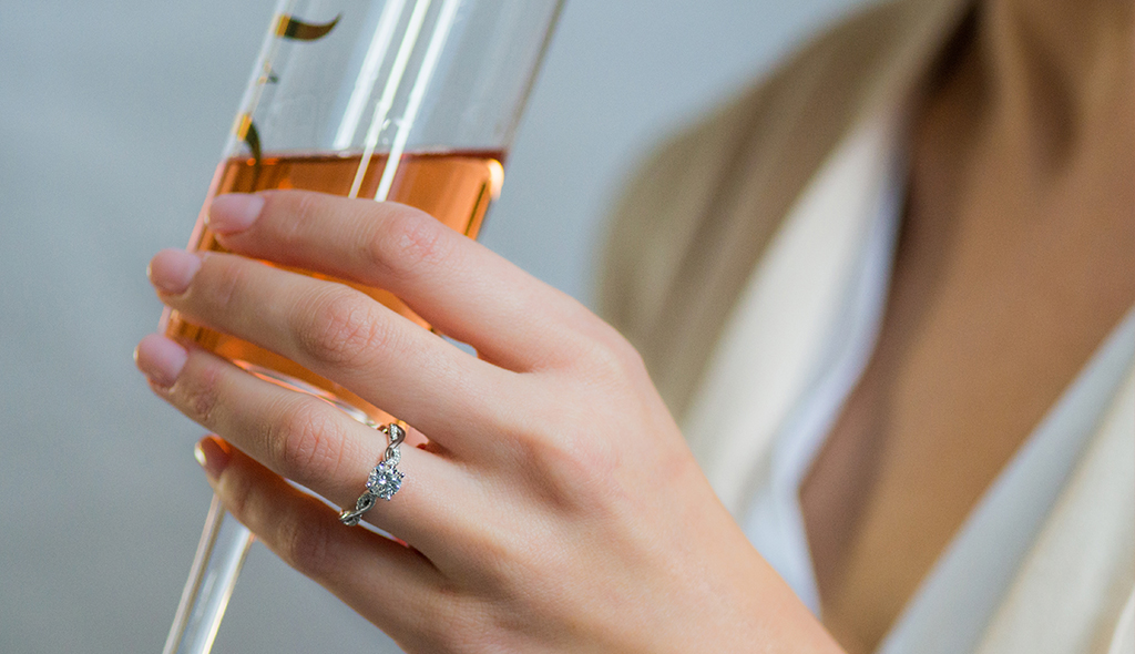 champagne glass with white gold engagement ring