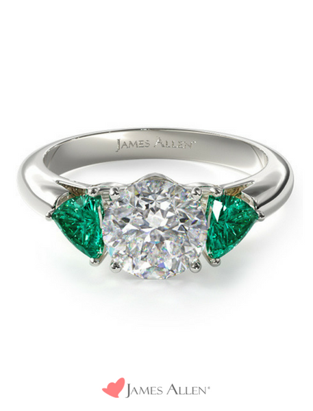 Round diamond engagement ring with emerald side stones
