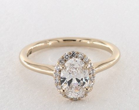 Oval halo engagement ring with plain band in yellow gold