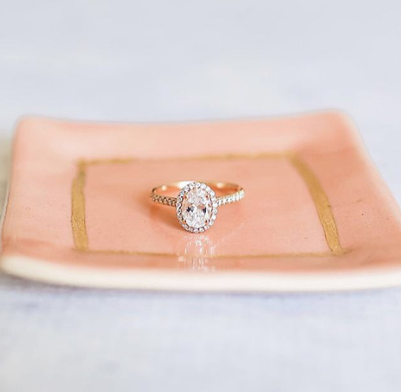 Rose gold pavé halo engagement ring with oval center