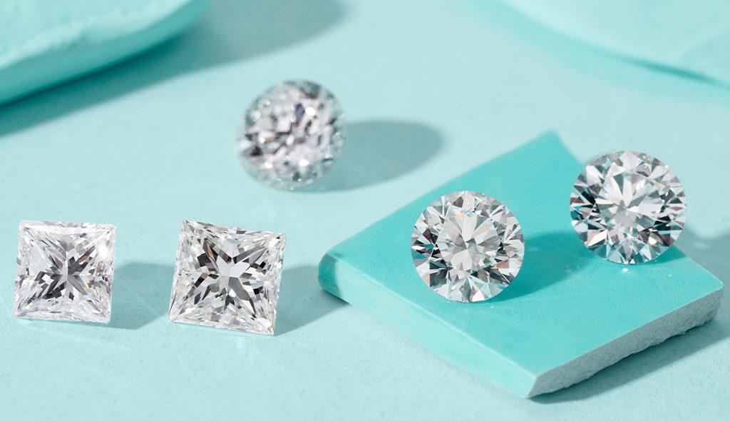 Loose princess-cut lab-created diamonds and loose round lab-created diamonds on a blue background