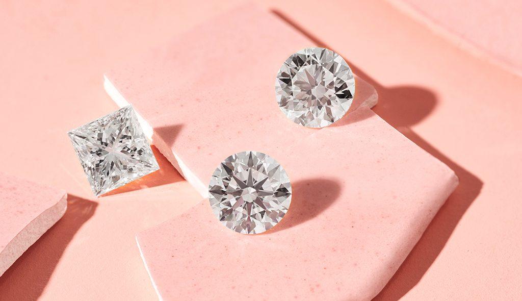 Loose princess-cut lab-created diamonds and loose round lab-created diamonds on a pink background