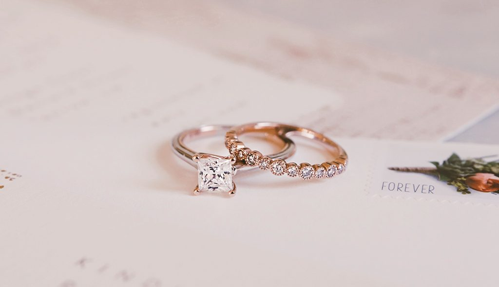 rose gold solitaire engagement ring and a rose gold wedding ring.
