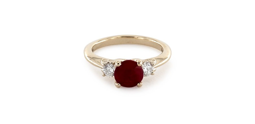 Affordable engagement rings: yellow gold three-stone engagement ring with round center ruby and diamond side-stones.