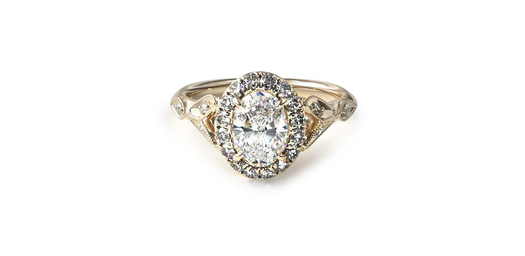 Affordable engagement rings: yellow gold navette leaf halo engagement ring with an oval-cut center diamond.