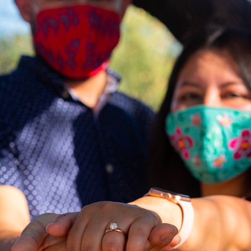 Fall Proposal Ideas: A newly-engaged, mask-wearing couple show off their sparkling engagement ring.