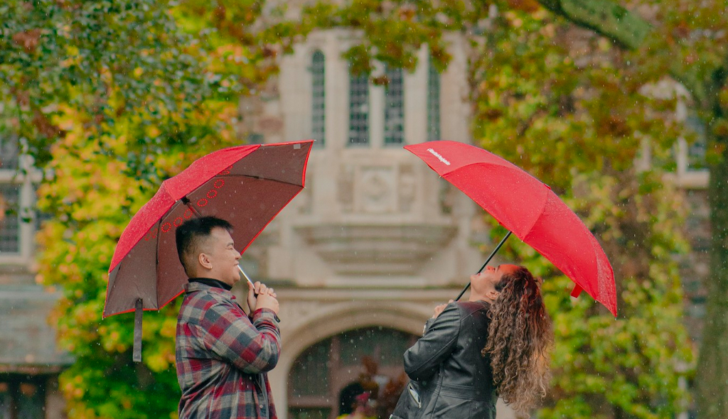 Fall Proposal Ideas: giggling newly-engaged couple holding red umbrellas in pouring rain