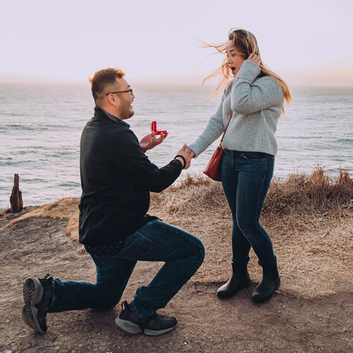 Fall Proposal Ideas: a man proposing on one knee on a windy coastal cliff.