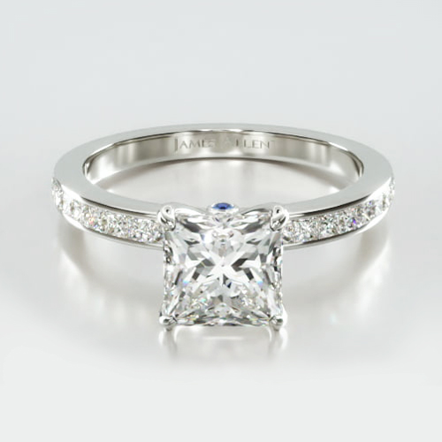 Channel Set Princess Cut Diamond Engagement Ring Embellished With a Four Prong Signature Head With Sapphire Bridge Accent