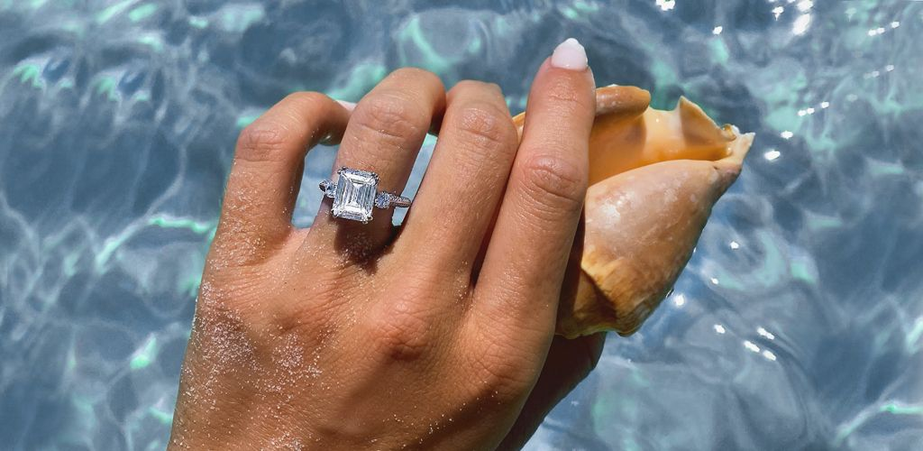 A person holding a sea shell above crystal clear water while showing off her diamond engagement ring.