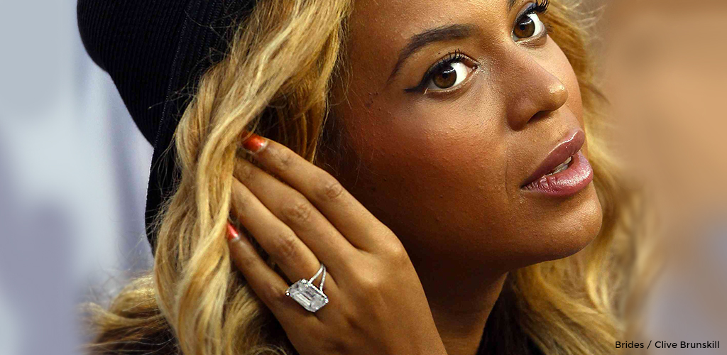 Beyoncé brushing back her hair while showing off her sparkling diamond engagement ring.