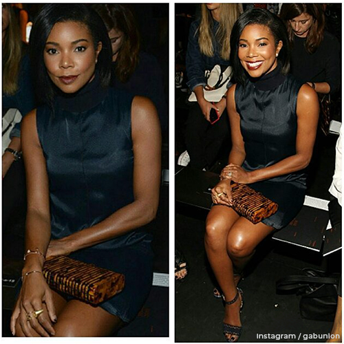 Gabrielle at a fashion show resting her hand on her knee, her engagement ring is on clear display.