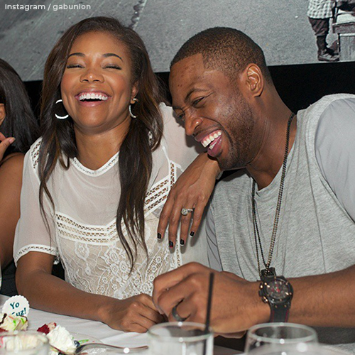 Gabrielle and Dwayne laughing together. Her engagement ring hand rests on his shoulder displaying the diamond.