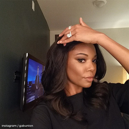 Gabrielle brushing back her hair while she shows off her sparkling diamond ring.
