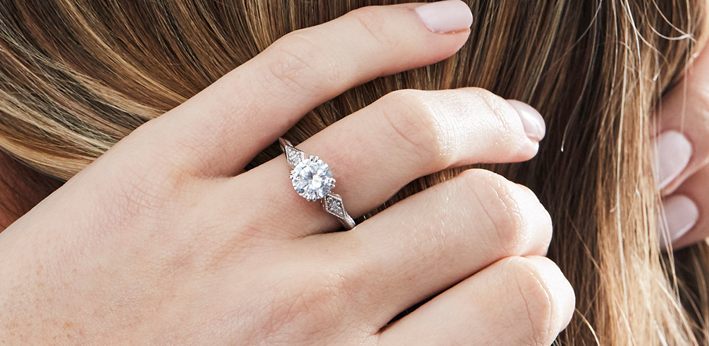 A woman adjusts her hair while displaying her vintage diamond engagement ring.
