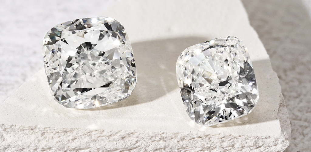 two different sized cushion-cut diamonds sparkling on a gravel stone top.