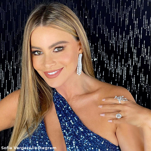 Sofia looking happy with an array of different jewelry. She lifts up her hand to show off both her diamond engagement ring as well as a chunky diamond ring. She's also wearing drooping diamond earrings.