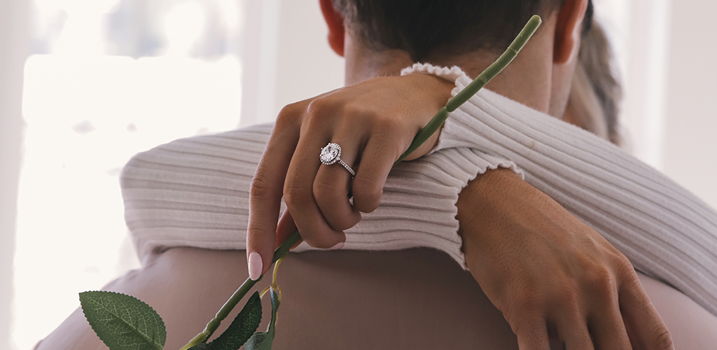 A picture of an engaged couple. The woman has her arms wrapped around his neck and is showing off her diamond ring.